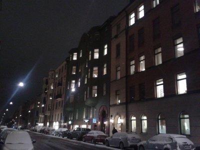 Pojedynczy przechodnie na ulicy, adwentowo oświetlone okna mieszkań.